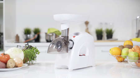 White electric mincer machines for minced meat per minute, make sausages, mashed berries, squeeze juice and chop vegetables. Meat mincer of increased power is reliable assistant in kitchen. Stockfoto