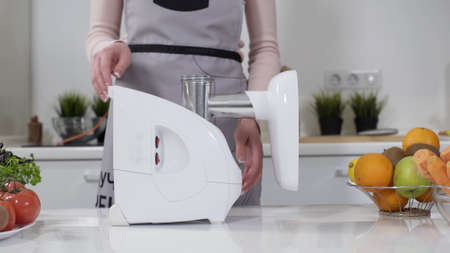 Woman flips meat grinder on its side. electric meat grinders from fresh beef at home. Stable non-slip rubber feet for reliable fixing meat mincer on table surface.