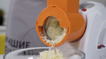 Mincer machine cuts vegetable in kitchen. White electric mincer machines for minced meat per minute, make sausages, mashed berries, squeeze juice and chop vegetables. Pile of chopped potatoes.