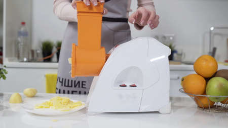 Mincer machine cuts vegetable in kitchen. White electric mincer machines for minced meat per minute, make sausages, mashed berries, squeeze juice and chop vegetables.