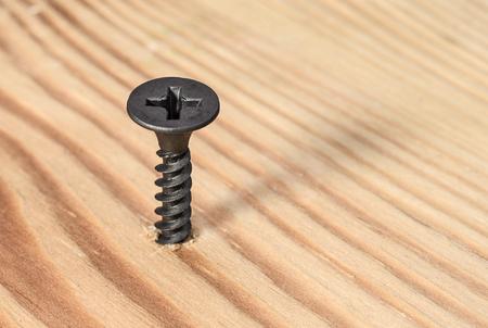 Black screw screwed into wood Stock Photo