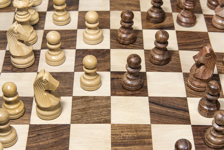 Wooden chessboard with figures closeup