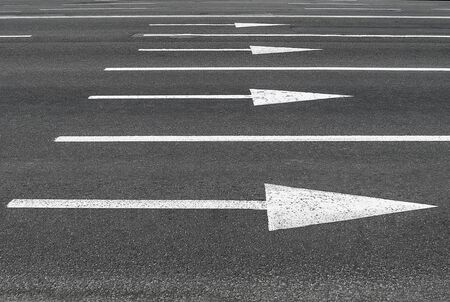 Road markings in the form of arrows on the asphalt. Roads and urban infrastructure.