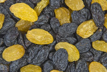 Black and yellow dry berries of raisins close up. Sweets and desserts.