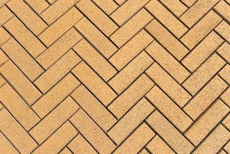 Brown brickwork of herringbone pattern. Textures and backgrounds