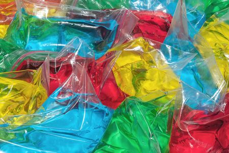 Polyethylene packs filled with multicolored transparent liquids. Abstract backgrounds and textures