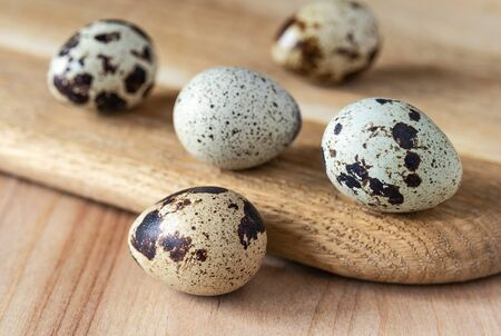 Quail eggs on the wooden kitchen board. Food and drink Фото со стока
