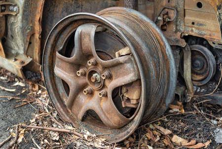 Rusty burnt car wheel rim with brake caliper. Automotive and car repair