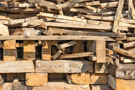 Heap of dry wooden boards, bars and sawn timber. Construction materials and repair. Backgrounds and textures
