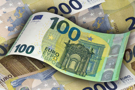 The one hundred EURO banknote on the background of two hundred EURO bills. Money, business and finances