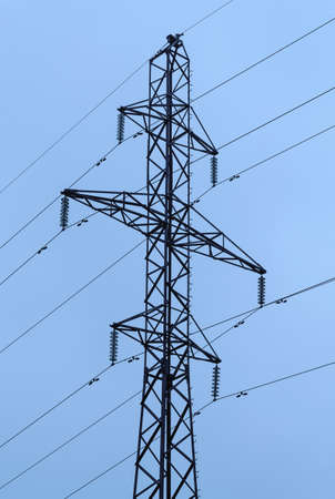 Pylon of power line against light blue background. Electricity, industrial and technologies 免版税图像