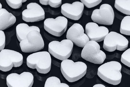 Pills in the form of white hearts on a dark background. Healthcare and medicine