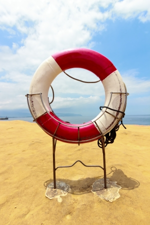 beach buoy: White life buoy with rope on the beach