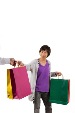 Shopping woman giving shopping bags to another person on white background at copy space  Young woman mixed race Taiwan   Chinese Asian shopper smiling happy Stock Photo - 21190561