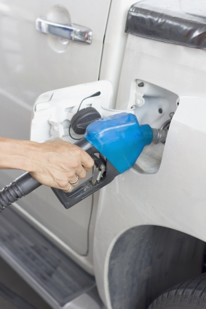 A hand filling up a dirty car with diesel  photo