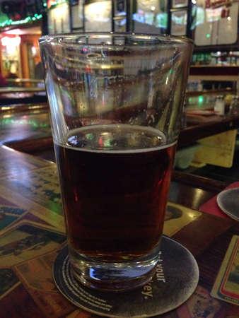 Glass of beer in bar Imagens