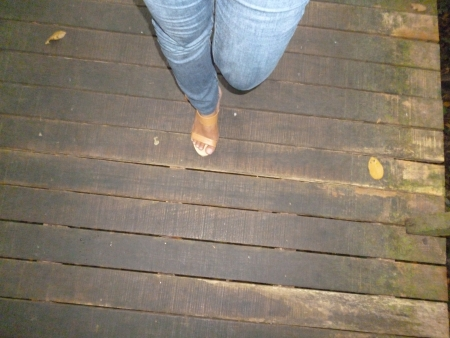 sandakan: woman s leg walking at the wooden bridge