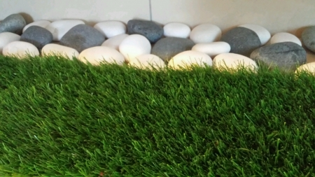 Close up pebbles with artificial grass