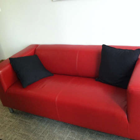black: Red couch with black pillows  Stock Photo