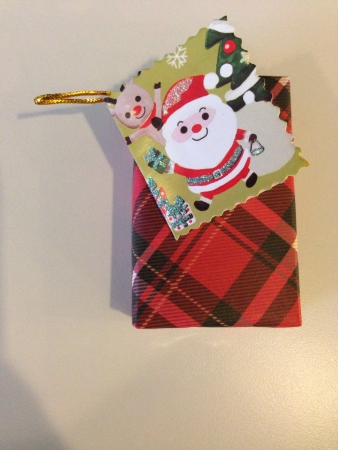 Christmas gift wrapped in checkers design wrapper  with a Santa card on top