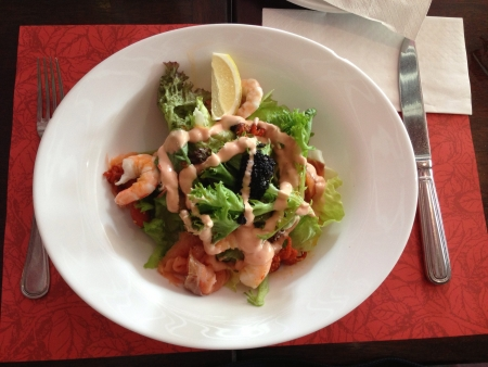 Seafood salad served on dining table with red placemat