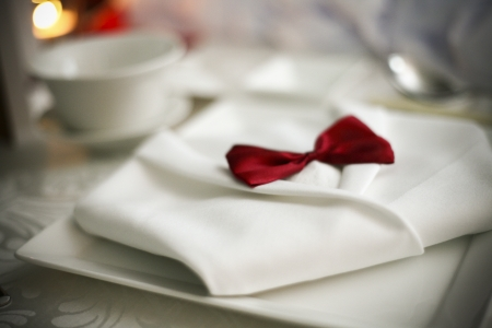 Beautiful napkin folding dinner jacket with a red bow on a plate