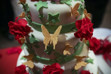Close up shot of 3 tier wedding cake with roses and butterflies