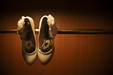 Creative shot of White wedding heels hanging on bar