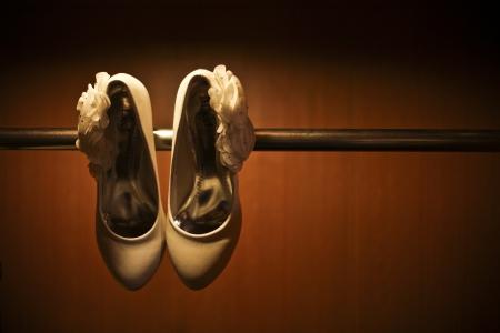 Creative shot of White wedding heels hanging on bar