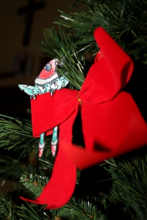 Green Evil elf with christmas hat hiding behind a red ribbon on a Christmas tree Stock Photo