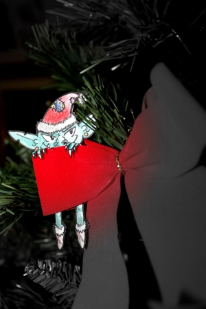 Green Evil elf with christmas hat hiding behind a red ribbon Stock Photo
