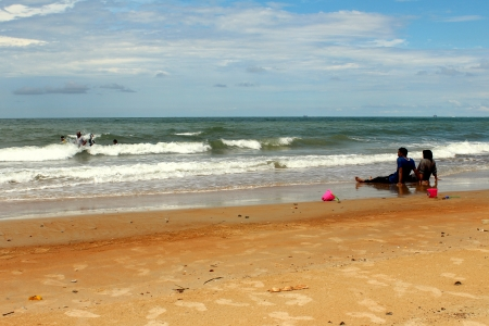 Couple enjoying beauty of the beach with clear blue sky and golden sand in Port Dickson