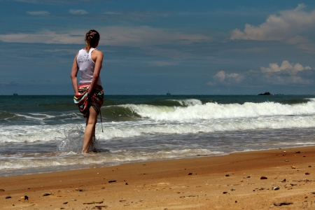 Rear view of female walking along the shore enjoying small current waves Editorial