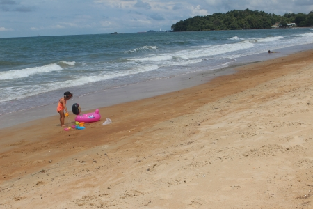 Little girl playing with pink float at Port Dickson beach