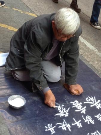 Old man writing using sand begging for money along Tung Choi Street, Hong Kong