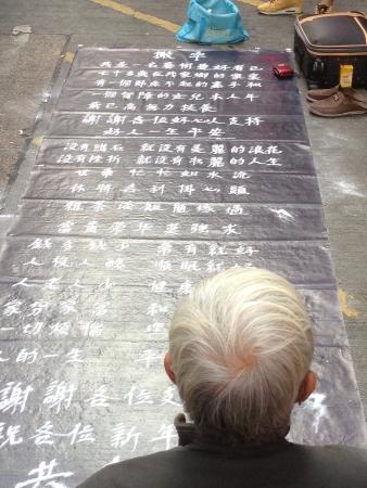 Old Asian man writing using sand begging for money along Tung Choi Street, Hong Kong Stock Photo