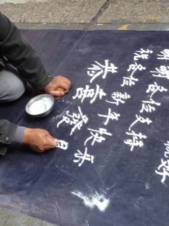 Close up of old Asian man sand writing begging for money along Tung Choi Street, Hong Kong