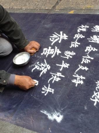 Close up of old Asian man sand writing begging for money along Tung Choi Street, Hong Kong2014