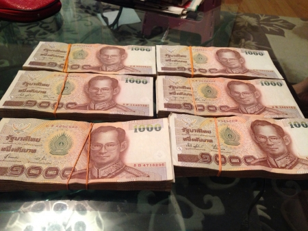 Stacks of Thai Baht on table