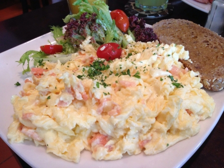 Scrambled eggs with salmon and bacon Stock Photo