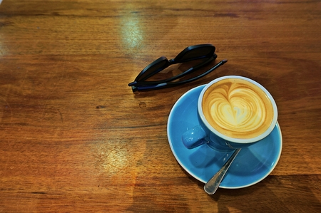 Coffee with art and sunglass on wooden table Stock Photo