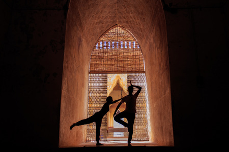 Man and woman yoga in silhouette