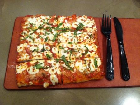 margarita pizza: Margarita pizza with silverware at restaurant
