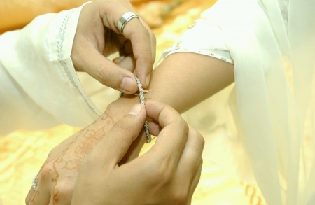 Hand of groom helping a bride wearing a bracelet Stock Photo - 24267207