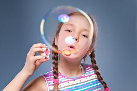女の子は非常に大きなバブルを膨らま