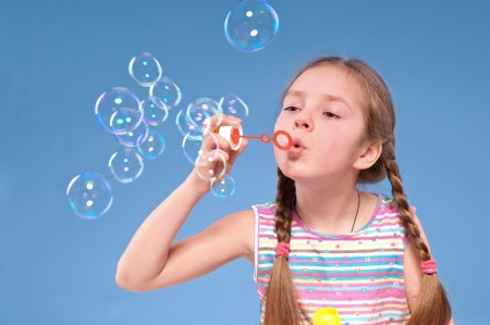 little girl blowing soap bubbles Standard-Bild