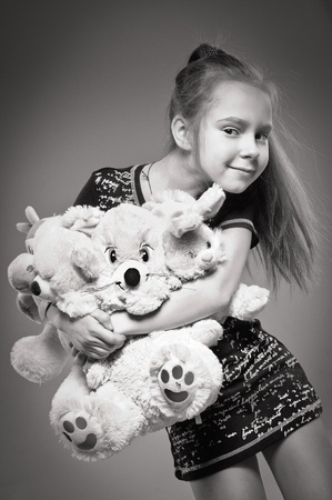 armful: girl holds the armful of toys Stock Photo