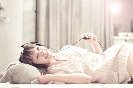 young woman lying on the floor with a toy. She listens to music and smiling Stock Photo - 12802931