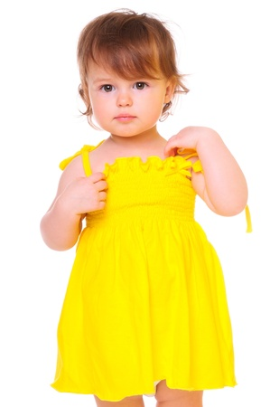 cute little girl in a yellow dress. portrait of a close-up in the studio. isolated on white photo