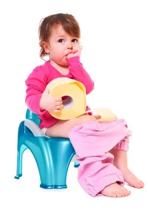 vasino: Pretty ragazza è seduta sulla pentola, in possesso di un rotolo di carta, succhiandosi il dito. isolato su bianco